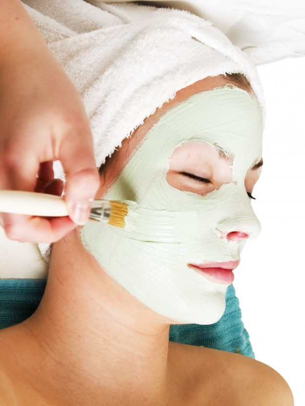 A detail image of a green apple mask being applied at a beauty spa.